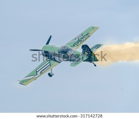 BUCHAREST, ROMANIA - SEPTEMBER 5, 2015. Aerobatic airplane pilot Jurgis Kairys training in the sky of the city. Colored airplane with trace smoke, airbandits, aeroshow.