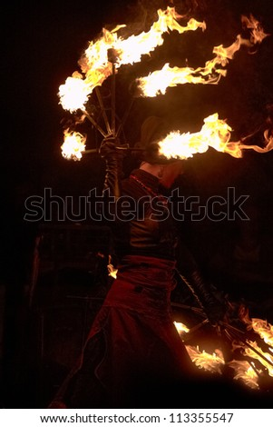 BUCHAREST, ROMANIA - SEPTEMBER 13: Lara Castiglioni performs with burning torches during B-FIT in the Street, International Street Theater Festival on September 13, 2012 in Bucharest, Romania.