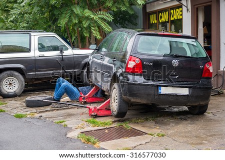 BUCHAREST, ROMANIA - SEPTEMBER 12, 2015: Man working under his Wolkswagen Polo car at a small car service trying to fix a steering system issue due to bad roads - stock photo