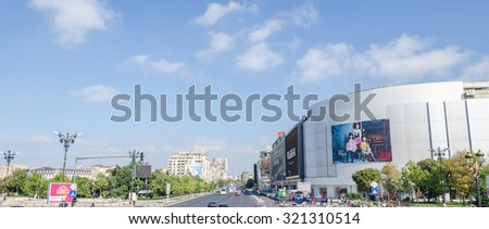 "BUCHAREST, ROMANIA - SEPTEMBER 19, 2015. The square ""Piata Unirii"" with shops, traffic cars, people."