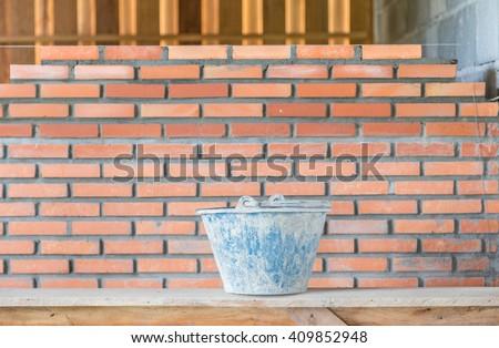 bucket and bricks. Under construction. - stock photo