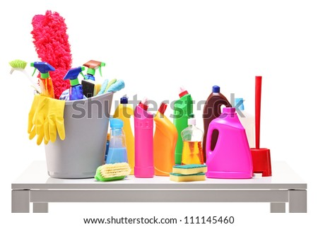 Bucket and cleaning supplies on a table isolated on white background - stock photo