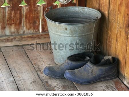 Bucket and galoshes are on a porch of the rural house - stock photo