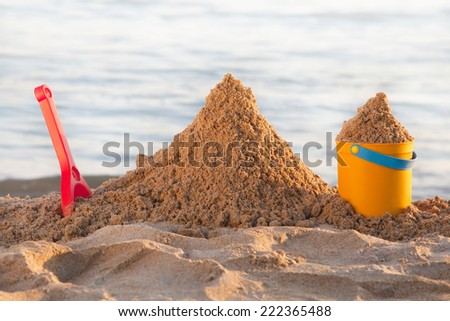 Bucket and shovel in the sand at the beach - stock photo