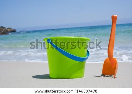 Bucket and shovel on a sandy beach - stock photo