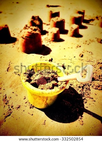 Bucket and spade with sand castles - stock photo