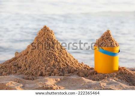 Bucket and the sand on the beach - stock photo