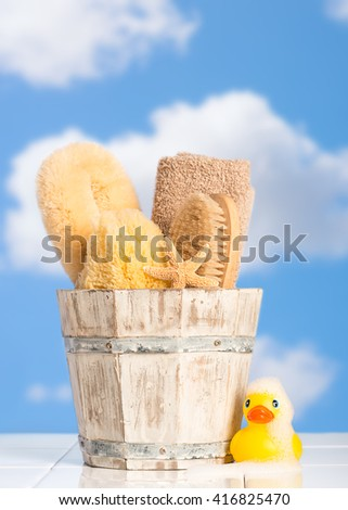 Bucket filled with bathroom objects with rubber duck covered in soap suds