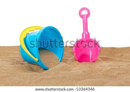 Bucket full and shovel on the sand with copy space on a white background. Shallow depth of field - stock photo