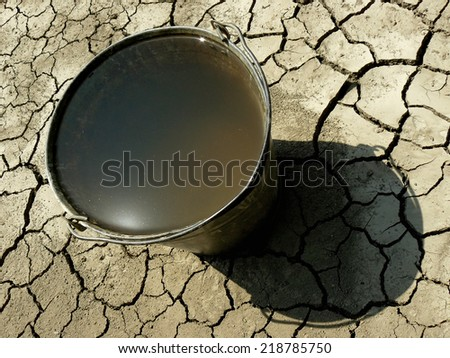 bucket full of water on dry soil background - stock photo