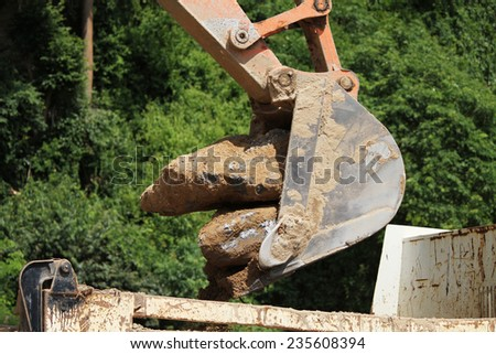 Bucket of Backhoe machine under removal of junk concrete at site. - stock photo