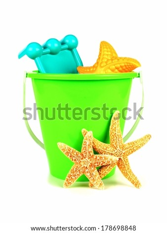 Bucket of beach toys with starfish on a white background                    - stock photo
