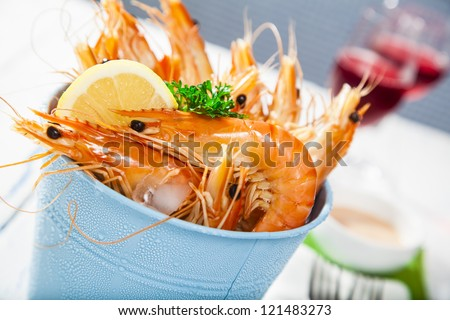 Bucket of king prawns on ice with lemon, sauce and two glasses of wine