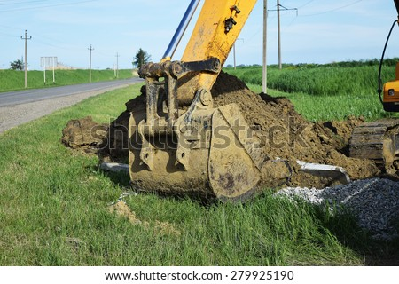 Bucket of the excavator on installation of the basis of electrocolumns. - stock photo