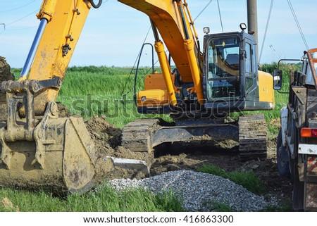 Bucket of the excavator on installation of the basis of electrocolumns. - stock photo