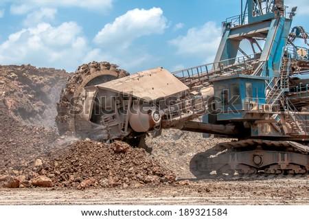 Bucket- wheel excavator closeup in the open-pit mine - stock photo