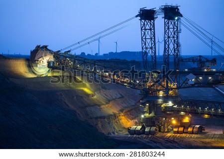 bucket-wheel excavator in open-cast coal mining in germany in the evening - stock photo