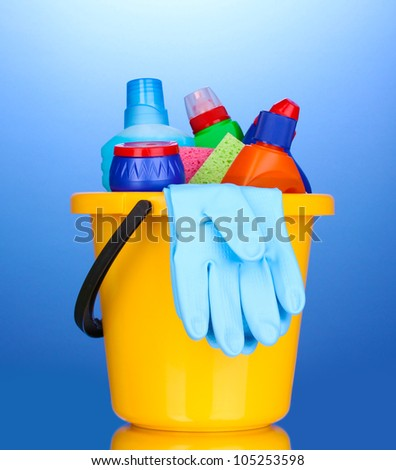 Bucket with cleaning items on blue background - stock photo