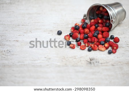 Bucket with fresh blueberries and strawberries on a wooden background.  - stock photo