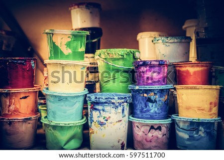 Buckets of liquid paint standing in a workshop. Vintage colors