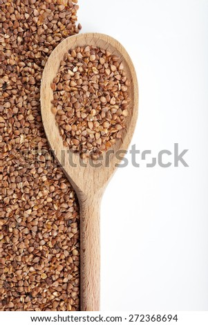 Buckwheat and spoon on a white background. - stock photo