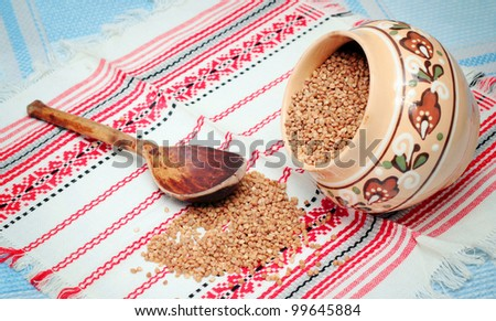 Buckwheat and wooden spoon on white fabric