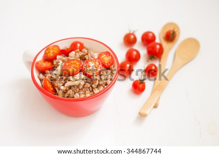 buckwheat cereal with tomatoes in a bowl on a table, selective focus
