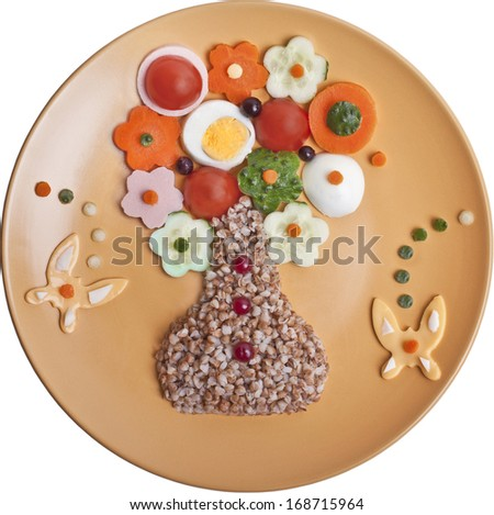 Buckwheat cereal with vegetables, cheese and eggs are laid in the form of a vase with flowers - stock photo