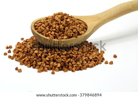 Buckwheat grains in wooden spoon on white isolated background