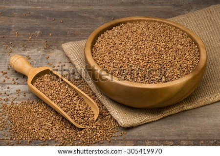 Buckwheat groats in a bowl and wooden scoop with buckwheat on grunge background - stock photo