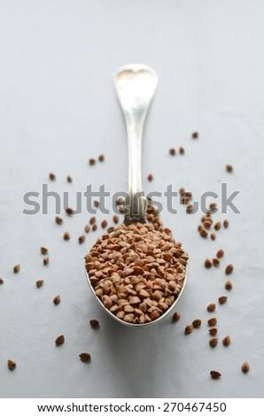 Buckwheat groats on a spoon. Selective focus. - stock photo