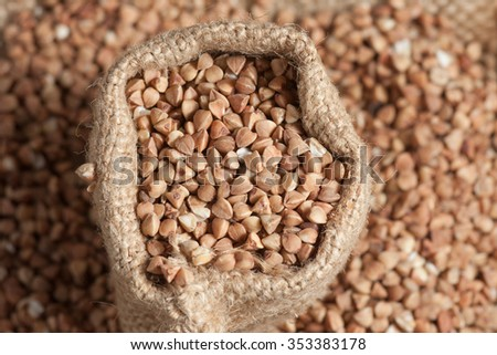 buckwheat groats on wooden and sacking background. healthy organic food concept - stock photo