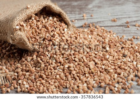 buckwheat groats on wooden and sacking background. healthy organic food concept
