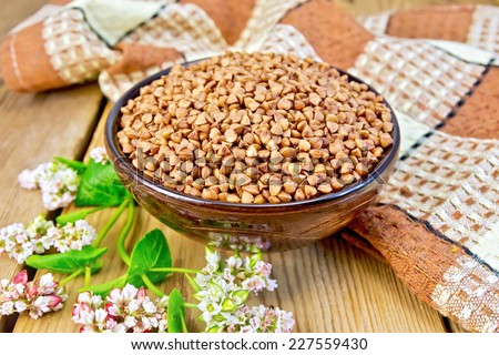 Buckwheat in a bowl with a flower and a napkin on a wooden boards background