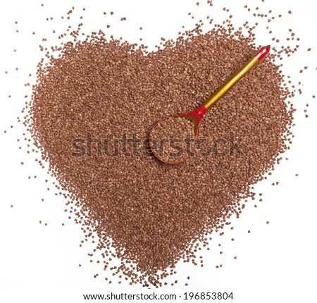 Buckwheat in the shape of a heart with a wooden spoon - stock photo