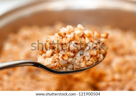 Buckwheat in the spoon with boiling saucepan in background - stock photo