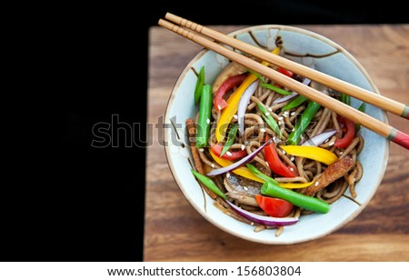 Buckwheat noodles (soba) with chicken and vegetables on the wooden board and black background - stock photo