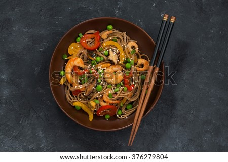 Buckwheat noodles with seafood in a bowl, top view, horizontal