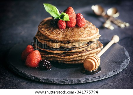 Buckwheat pancakes with berry fruit and honey.Selective focus - stock photo