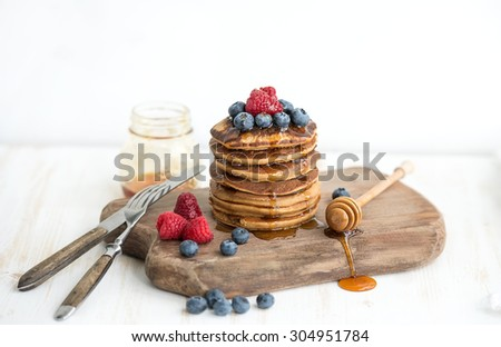 Buckwheat pancakes with fresh berries and honey on rustic wooden board, white backdrop - stock photo