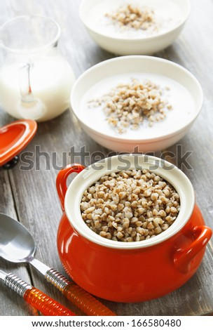 Buckwheat porridge in the orange pot and milk on the table