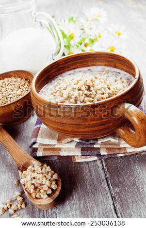 Buckwheat porridge with milk in the bowl on the table