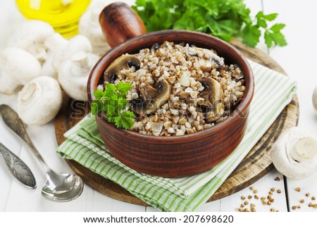 Buckwheat porridge with mushrooms in a ceramic pot on the table