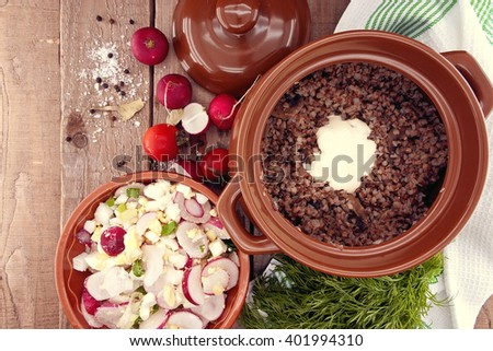 Buckwheat porridge with salad from radish and egg in a ceramic pot. Top view. - stock photo