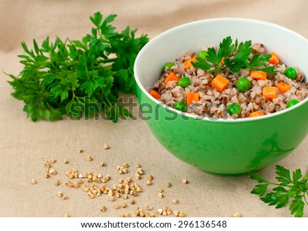 Buckwheat porridge with vegetables over textile background, selective focus