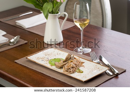 Buckwheat soba noodles with lamb tongue served with white wine at restaurant - stock photo