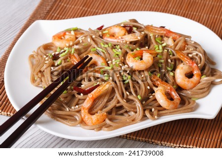 buckwheat soba noodles with shrimp and sesame seeds on a plate close-up. horizontal  - stock photo