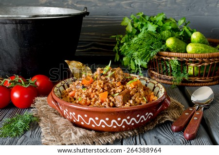 Buckwheat with meat and vegetables on wooden table, rustic style - stock photo