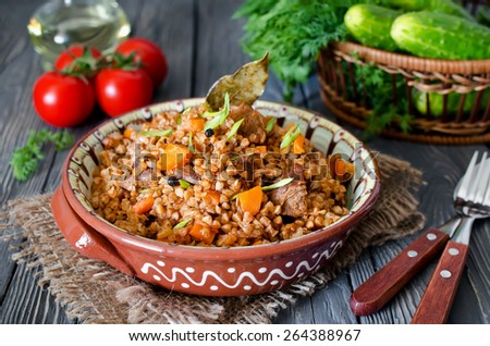 Buckwheat with meat and vegetables on wooden table, rustic style