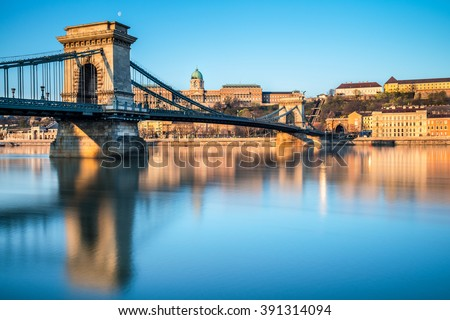 Budapest Castle and famous Chain Bridge in Budapest early morning. Focus on the bridge. - stock photo